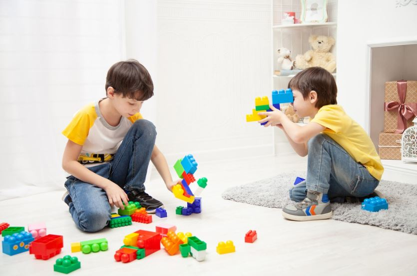 2 young buys playing with big stackable block toys